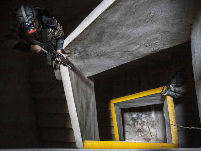 In this Wednesday, Dec. 5, 2012 photo, Free Syrian Army fighters aim their weapons inside an abandoned building during heavy clashes with government forces in Aleppo, Syria. (AP Photo/Narciso Contreras)