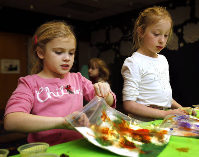 Greta Mansell, 7, and Lydia Stuart, 8, make paintings inside plastic bags during the after-school special story time at the Norman Public Library. PHOTO BY STEVE SISNEY, THE OKLAHOMAN <strong>STEVE SISNEY</strong>