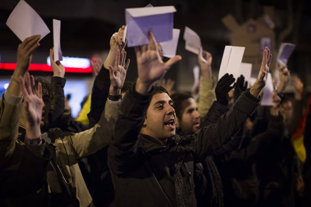 Protesters shout slogans during a demonstration against corruption in front of the Popular Party offices in Barcelona, Spain, Saturday, Feb. 2, 2013. Spain's prime minister has denied media reports that allege he and members of his governing Popular Party accepted or made under-the-table payments.  Attorney General Eduardo Torres-Dulce said Friday there is sufficient cause to investigate allegations of irregular financing within Rajoy's party. Leading newspaper El Pais has published details of secret papers belonging to former party treasurer Luis Barcenas allegedly documenting undeclared payments. (AP Photo/Emilio Morenatti)