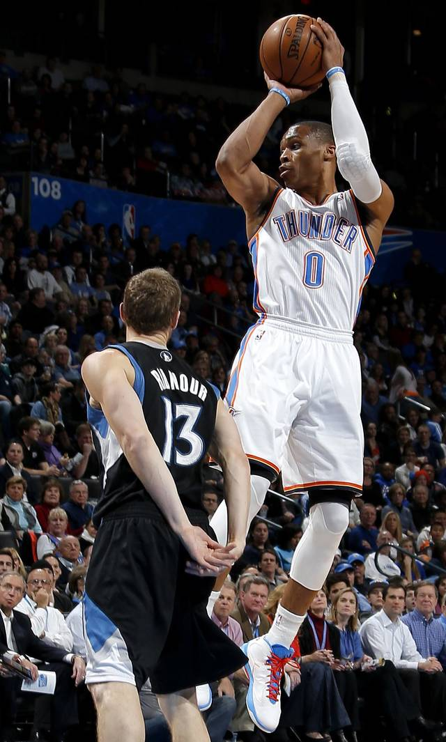 Oklahoma City's Russell Westbrook (0) passes over Minnesota's Luke Ridnour (13) during an NBA basketball game between the Oklahoma City Thunder and the Minnesota Timberwolves at Chesapeake Energy Arena in Oklahoma City, Wednesday, Jan. 9, 2013.  Photo by Bryan Terry, The Oklahoman