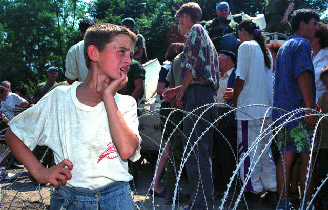"FILE This Thursday July 13, 1995 file photo shows a young Muslim refugee from Srebrenica watching as other refugees pass in a UN armored vehicle as they arrive at a U.N. base 12 kms south of Tuzla, 100kms (60 miles) north of Sarajevo. They are among the more than 5,000 refugees from the U.N. safe haven of Srebrenica in eastern Bosnia, which was captured by Bosnian Serb forces, and who arrived in Bosnian Government controlled territory in the past 24 hours. The indictment against Ratko Mladic, who went on trial Wednesday May 16, 2012 at the U.N. war crimes tribunal in the Hague, Netherlands, holds the former Bosnian Serb army commander ""individually criminally responsible for planning, instigating, ordering and/or aiding and abetting the crimes charged in this indictment."" Mladic is charged with 11 counts of genocide, crimes against humanity and violations of the laws and customs of war. Between July 1995 and November 1995, Mladic participated in the ""elimination"" of the Bosnian Muslims in the eastern enclave of Srebrenica by killing the men and boys, and forcibly removing the women, young children and some elderly men. Some 7,000 people were killed which is the worst carnage in Europe since World War II(AP Photo/Darko Bandic)"