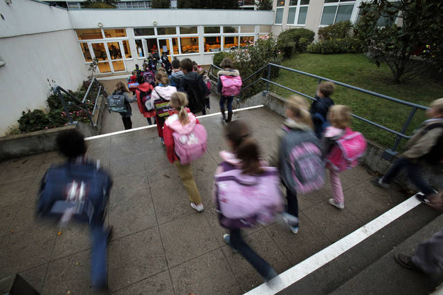 Students enter school of La Ronce in Ville d'Avray, west of Paris, Friday, Oct. 5, 2012. French children go to school four days a week with about two hours each day for lunch. And they have more vacation than their counterparts almost anywhere in the West. As a candidate, President Francois Hollande promised to change things by adding a fifth day of classes on Wednesday while shortening the school day and education minister, Vincent Peillon, will decide this month how to carry out the reform. (AP Photo/Christophe Ena)