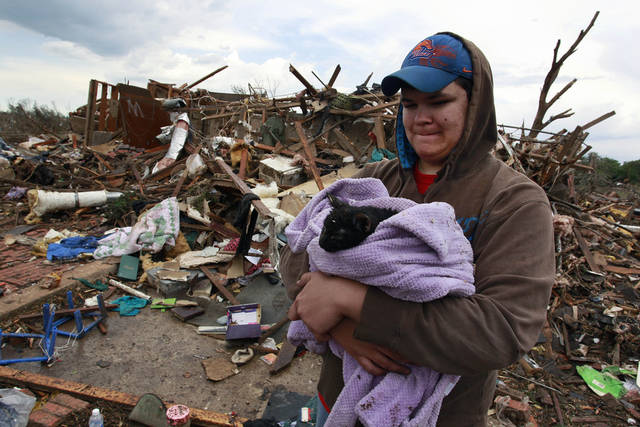 Austin Brock holds cat Tutti, shortly after the animal was retrieved from the rubble of Brock's home, which was demolished a day earlier when a tornado moved through Moore, Okla., Tuesday, May 21, 2013. A huge tornado roared through the Oklahoma City suburb Monday, flattening an entire neighborhoods and destroying an elementary school with a direct blow as children and teachers huddled against winds. (AP Photo/Brennan Linsley)