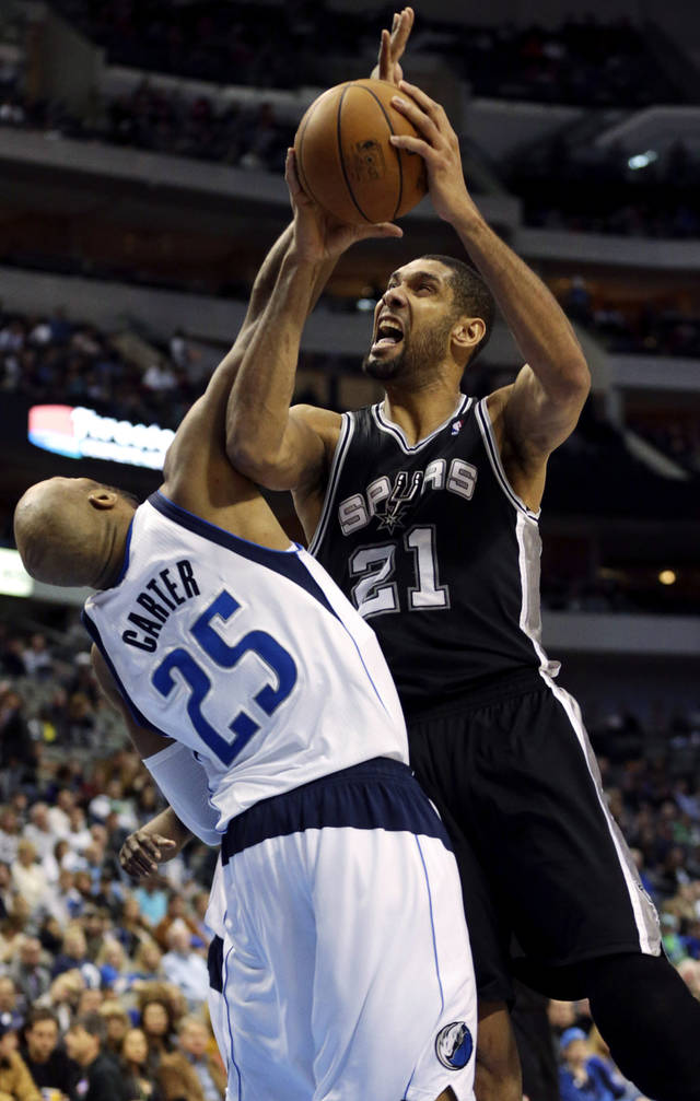 San Antonio Spurs forward Tim Duncan (21) takes a shot against Dallas Mavericks forward Vince Carter (25)  during the second half of an NBA basketball game in Dallas on Sunday, Dec. 30, 2012. San Antonio won 111-86. (AP Photo/Mike Fuentes)