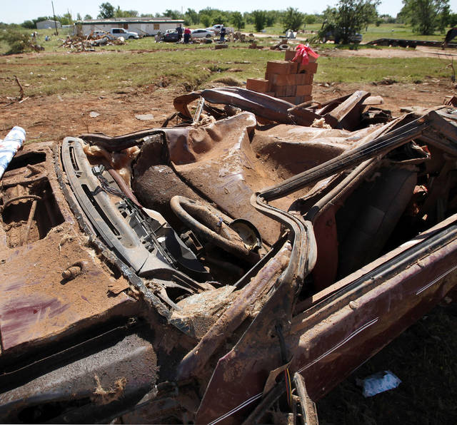 A flattened car sits in front of a damaged mobile home. Nine trailers were destroyed  and many others received major damage in the Hide-A-Way Mobile Home Park when a  killer tornado roared through sections of Woodward last weekend.   Two men and two girls died in the twister.  Photo taken Tuesday, April 17, 2012.   Photo by Jim Beckel, The Oklahoman