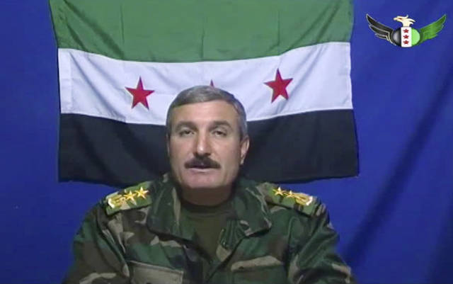 FILE - In this undated file photo, Syrian Commander Riad al-Asaad, who heads a group of Syrian army defectors appears on a video posted on the group's Facebook page. The Britain-based Syrian Observatory for Human Rights said Monday March 25, 2013 a bomb stuck to his car targeted Col. Riad al-Asaad during a visit to the town of Mayadeen in eastern Syria. The Observatory cited conflicting reports on al-Asaad's fate, with some saying he had been killed and others saying he lost a leg. There was no immediate claim of responsibility for the attack. (AP Photo/Free Syrian Army) THE ASSOCIATED PRESS HAS NO WAY OF INDEPENDENTLY VERIFYING THE CONTENT, LOCATION OR DATE OF THIS VIDEO IMAGE.