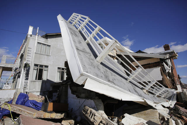 A storm-damaged beachfront house is shown in the Far Rockaways, Thursday, Jan. 31, 2013 in the Queens borough of New York. Carpenters, left, work on a neighboring house. Three months after Superstorm Sandy ravaged coastal areas in much of the Northeast, Congress on Monday, Jan. 28 passed a $50.5 billion emergency aid package for storm victims. (AP Photo/Mark Lennihan)