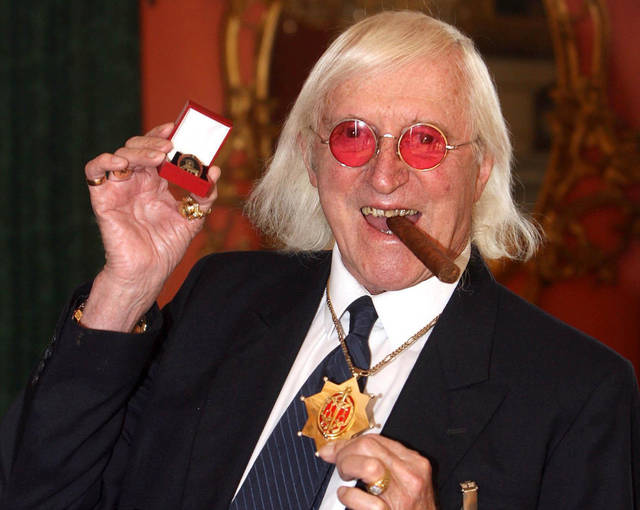 FILE This March 25, 2008 file photo shows Jimmy Savile showing a medal in London. Amid mounting complaints that British authorities for decades failed to properly examine allegations of child abuse, lawmakers called Tuesday Nov. 6, 2012 for a sweeping national inquiry into the issue. Allegations that renowned BBC children�s TV host Jimmy Savile abused hundreds of young people have prompted national debate, and led scores of adults to contact authorities about other, unrelated cases of sex offenses in the past. (AP Photo/Lewis Whyld/PA Wire)