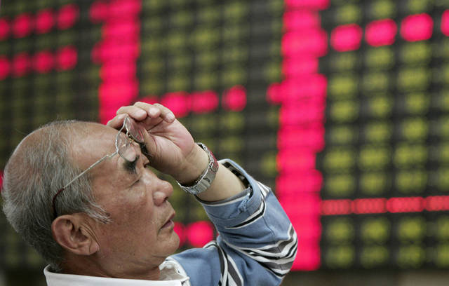An investor looks at the stock price monitor at a private securities company Monday June 4, 2012 in Shanghai, China. Chinese shares lost ground Monday, with the benchmark Shanghai Composite Index falling 2.73 percent, or 64.89 points, in its biggest drop in terms of points this year, to 2,308.55. (AP Photo)