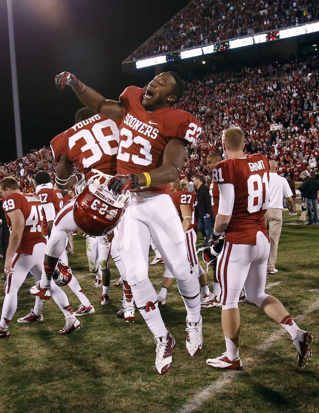 Oklahoma's Danzel Williams (23) and Brandon Young (38) leap at the conclusion of the Bedlam college football game in which  the University of Oklahoma Sooners (OU) defeated the Oklahoma State University Cowboys (OSU) 51-48 in overtime at Gaylord Family-Oklahoma Memorial Stadium in Norman, Okla., Saturday, Nov. 24, 2012. Photo by Steve Sisney, The Oklahoman