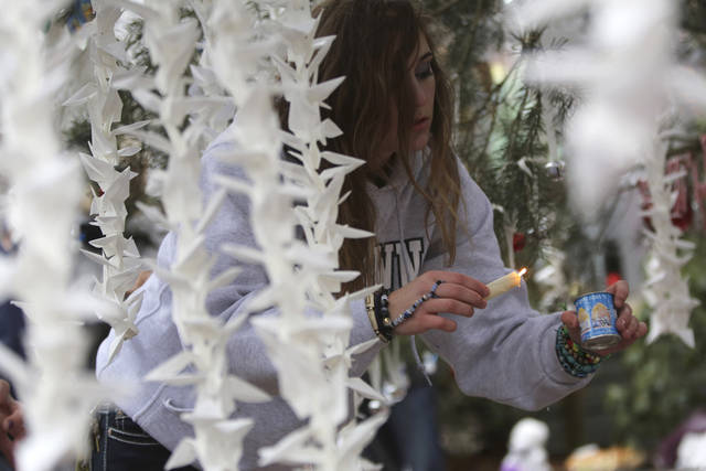 Jamie Duncan, 16, of Newtown, Conn., lights a candle at one of the makeshift memorials for the Sandy Hook Elementary School shooting victims, Monday,Dec. 17, 2012 in Newtown, Conn.  Authorities say gunman Adam Lanza killed his mother at their home on Friday and then opened fire inside the Sandy Hook Elementary School in Newtown, killing 26 people, including 20 children, before taking his own life. (AP Photo/Mary Altaffer) ORG XMIT: CTMA104
