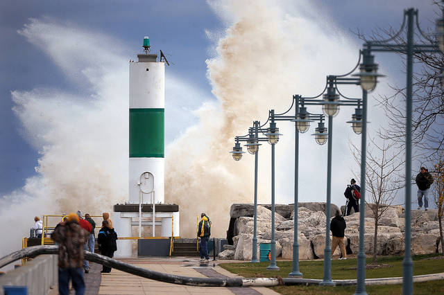A large crowd is drawn to the Lake Michigan shoreline in Kenosha, Wis. on Tuesday, Oct. 30, 2012 to watch big waves caused by winds from superstorm Sandy. (AP Photo/The Kenosha News, Bill Siel) ORG XMIT: WIKEN101