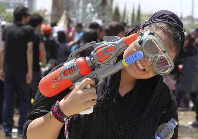 "In this picture taken on Friday, July 29, an Iranian woman poses with her water gun, during water fights at the Water and Fire Park in northern Tehran, Iran. Iran is trying to put down a new wave of civil disobedience - flash mobs of young people who break into boisterous fights with water guns in public parks. A group of water fighters was arrested over the weekend, and a top judiciary official warned Monday that ""counter-revolutionaries"" were behind them. Throughout the summer, Iranian police have been cracking down. In the first incident, in July, hundreds of young men and women held a water fight in Tehran's popular Water and Fire Park, spraying each other with water guns and splattering bottles of water on one another. Police detained dozens of those involved.(AP Photo/Milad Beheshti)"