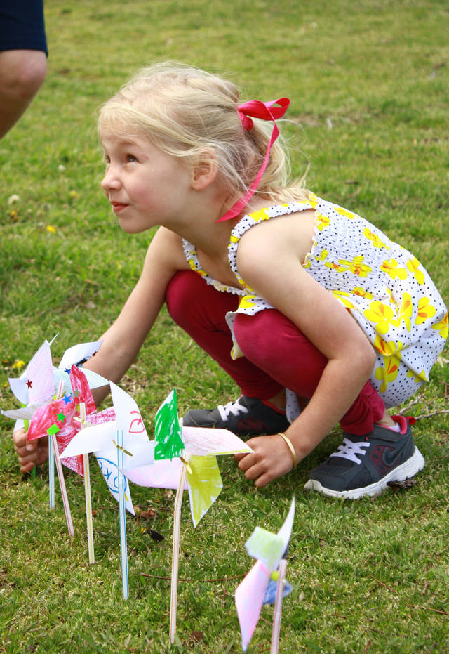 Molly Cook, 4, adds her pinwheel to a row of children's handmade art at a child abuse awareness event Saturday at Andrews Park in Norman. PHOTO BY LYNETTE LOBBAN, FOR THE OKLAHOMAN <strong></strong>
