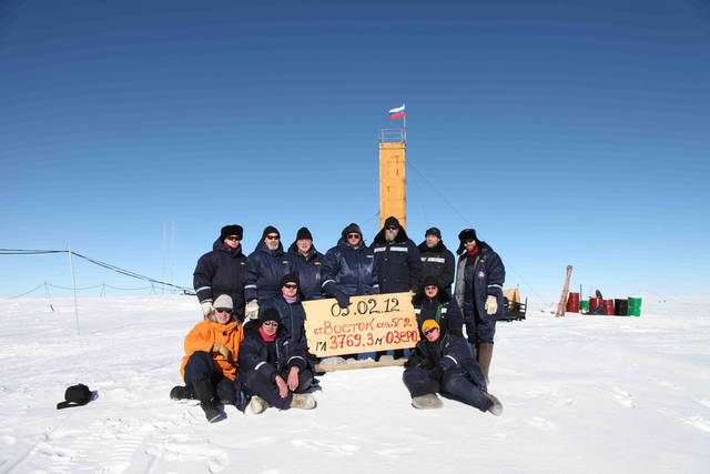 "In this Monday, Feb. 6, 2012 photo provided by Arctic and Antarctic Research Institute of St. Petersburg,   Russian researchers at the Vostok station in Antarctica pose for a picture after reaching subglacial lake Vostok. Scientists hold the sign reading ""05.02.12, Vostok station, boreshaft 5gr, lake at depth 3769.3 meters."" Russian scientists said Monday that a new form of microbial life has been found in water samples taken from the giant freshwater lake hidden under kilometers of Antarctic ice. (AP Photo/Arctic and Antarctic Research Institute Press Service, HO)"