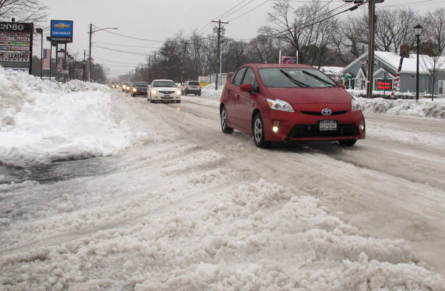 Vehicles try to maneuver across snow and ice-covered state Route 112 in Medford, N.Y., Monday, Feb. 11, 2013. While major highways on eastern Long Island were beginning to recover from a weekend blizzard, many local roads remained covered in snow and ice two days after the storm. (AP Photo/Frank Eltman)