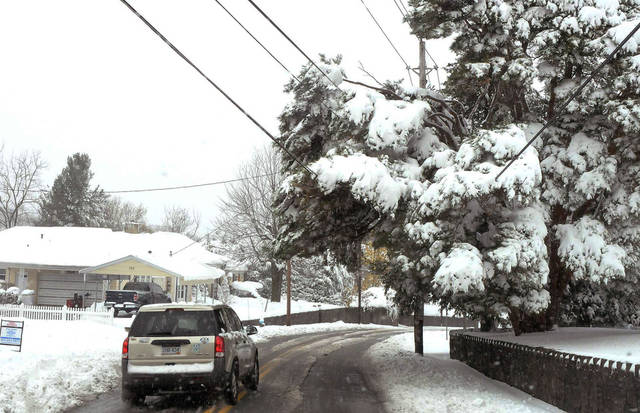 Snow pushes tree branches down on powerlines off of North Kanawha Street in Beckley, W.Va., on Tuesday, Oct. 30, 2012. Sandy, the storm that made landfall Monday, caused multiple fatalities, halted mass transit and cut power to more than 6 million homes and businesses. (AP Photo/The Register-Herald, Chris Tilley) ORG XMIT: WVBEC104