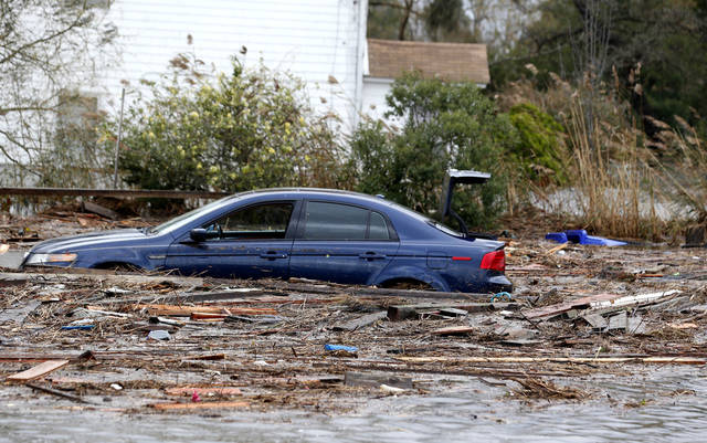 <p>A vehicle is seen in floodwaters the morning after hybrid storm Sandy rolled through, Tuesday, Oct. 30, 2012, in Brick, N.J. Locals say there were many houses on the beach front that are now vanished. Sandy caused multiple fatalities, halted mass transit and cut power to more than 6 million homes and businesses. (AP Photo/Julio Cortez)</p>
