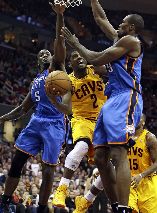 Cleveland Cavaliers' Kyrie Irving (2) shoots to the basket against Oklahoma City Thunder's Kendrick Perkins (5) and Serge Ibaka (9), from the Republic of Congo, during the fourth quarter of an NBA basketball game on Saturday, Feb. 2, 2013, in Cleveland. The Cavaliers won 115-110. (AP Photo/Tony Dejak) ORG XMIT: OHTD109