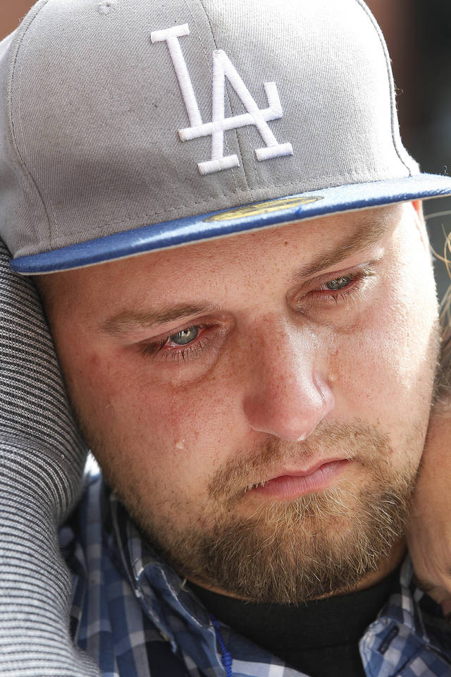 Rob Preece Jr., brother of fatally stabbed Los Angeles Dodgers fan Jonathan Denver, listens as the family makes a public plea for witnesses to Wednesday's stabbing, during a news conference outside AT&T Park before the Giants' baseball game in San Francisco, Sunday, Sept. 29, 2013. Denver, 24, was fatally stabbed following a Dodgers-Giants game. (AP Photo/Tony Avelar)