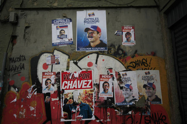 Election campaign posters promoting Venezuela's President Hugo Chavez and opposition presidential candidate Henrique Capriles cover a wall in Caracas, Venezuela, Friday, Oct. 5, 2012. Venezuelans head to the polls Sunday to vote in their country's presidential election, deciding on whether to keep Chavez or seek change with opposition candidate Henrique Capriles. (AP Photo/Ariana Cubillos)