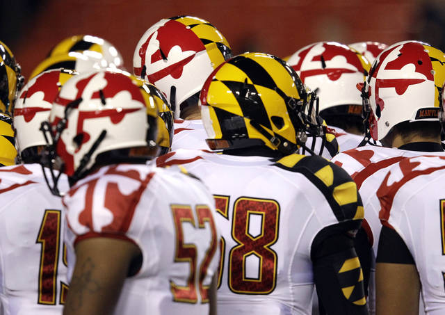 FILE - In this Nov. 12, 2011 file photo, members of the Maryland football team huddle before an NCAA college football game against Notre Dame, in Landover, Md. The roots of the uniform craze in college football can be traced to 1998 when Oregon and Nike began tinkering with tradition and going with a high-tech look. (AP Photo/Patrick Semansky, File)