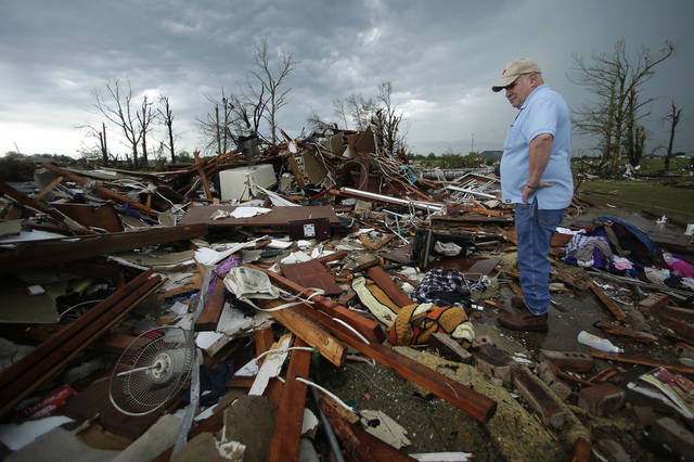 Monty Montgomery surveys the scene as he prepares to clean up a friend's tornado-ravaged home Thursday, May 23, 2013, in Moore, Okla. Cleanup continues three days after a huge tornado roared through the Oklahoma City suburb, flattening a wide swath of homes and businesses. (AP Photo/Charlie Riedel)