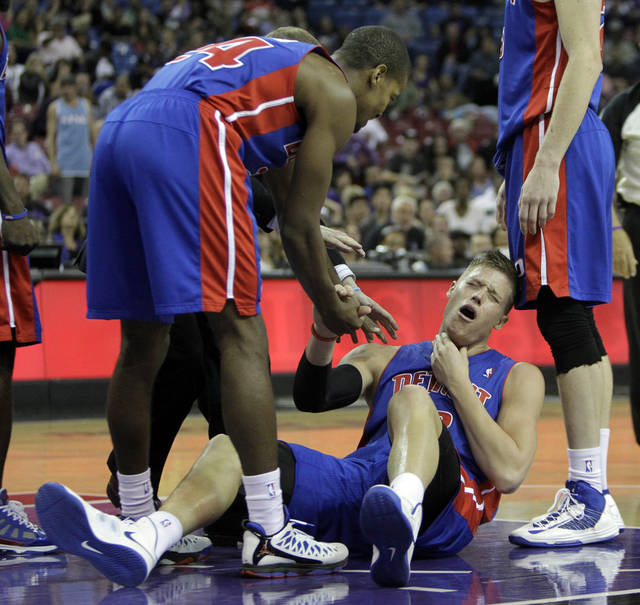 Detroit Pistons forward Jonas Jerebko, of Sweden, right, gets help from teammate Kim English, left, after was elbowed in the throat by Sacramento Kings forward Thomas Robinson during the second half of an NBA basketball game in Sacramento, Calif., Wednesday, Nov. 7, 2012. Robinson was given a flagrant foul and ejected from the game. The Kings won 105-103.(AP Photo/Rich Pedroncelli)