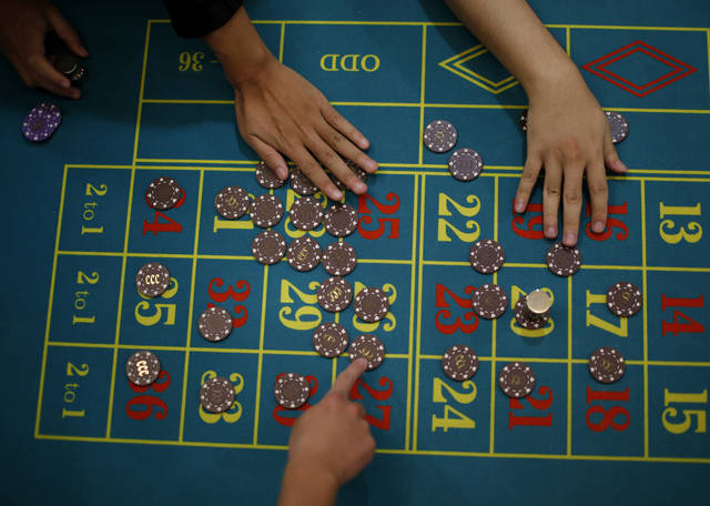 In this Oct. 25, 2012 photo, a gambling school students take practice on a table in Macau, China. Hordes of Chinese high rollers flooding into Macau have turned the city into an Asian casino boomtown but they�re also posing a challenge for China�s next generation of leaders.(AP Photo/Vincent Yu)