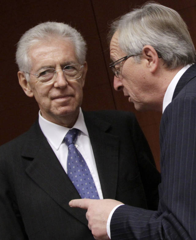 Luxembourg's Prime Minister Jean-Claude Juncker, right, speaks with Italian Prime Minister and Finance Minister Mario Monti during a round table meeting of the eurogroup at the EU Council building in Brussels on Tuesday, Nov. 29, 2011. The 17 finance ministers of countries that use the euro converged on EU headquarters Tuesday in a desperate bid to save their currency and to protect Europe, the United States, Asia and the rest of the global economy from a debt-induced financial tsunami. (AP Photo/Virginia Mayo)