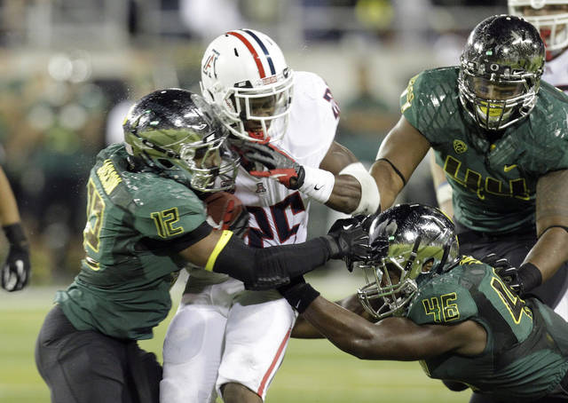 Arizona running back Ka'Deem Carey (25) is sandwiched by Oregon defenders, from left, Brian Jackson, Michael Clay and DeForest Buckner during the second half of their NCAA college football game in Eugene, Ore., Saturday, Sept. 22, 2012. Oregon won 49-0.(AP Photo/Don Ryan)