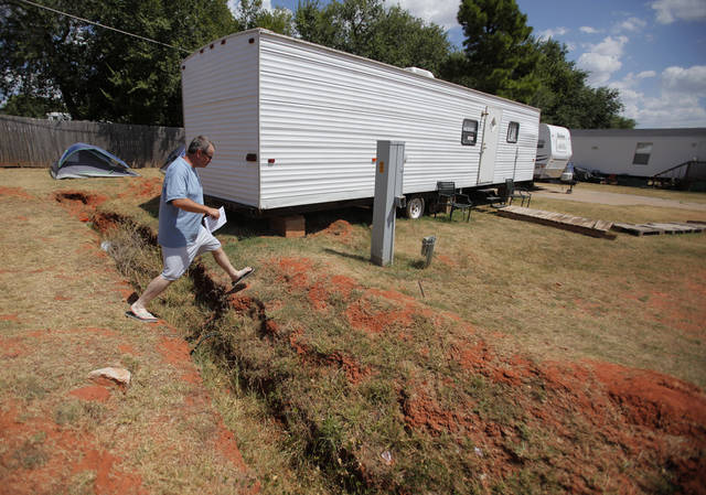 Bobby Miller crosses a ditch from his camp site at the Hand Up Ministry in Oklahoma City, Wednesday, July 25, 2012.  Photo by Garett Fisbeck, The Oklahoman Archives