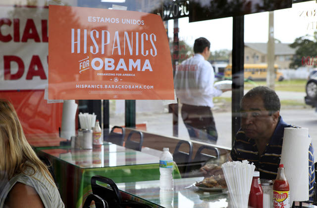FILE - In this Oct. 26, 2012, file photo, Spanish language election campaign signs promoting President Barack Obama hang on the windows at Lechonera El Barrio Restaurant in Orlando, Fla. Hispanics supported President Barack Obama over Republican Mitt Romney by almost 3-to-1 and put Republicans on notice they must take real steps to win over the nation�s largest minority group if they want to win the presidency again. Exit polls say that Romney, who has backed hardline immigration measures, won only 27 percent of Hispanics. (AP Photo/Julie Fletcher)