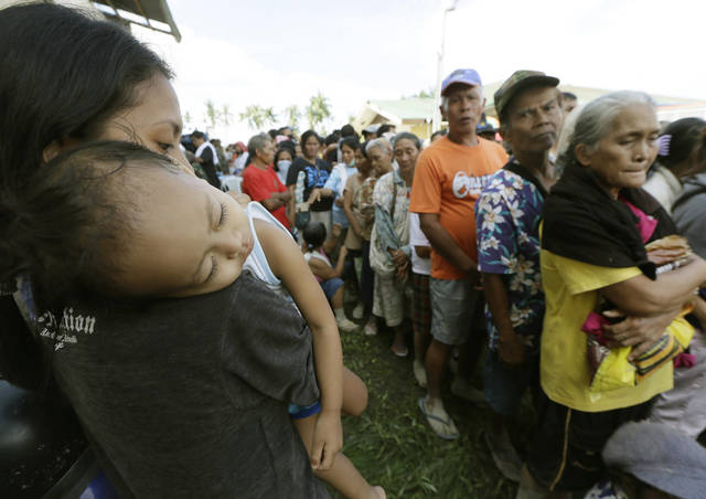 Residents, impacted by Tuesday's devastating typhoon,  line up for relief supplies at an evacuation center Thursday,  Dec. 6, 2012, at New Bataan township, Compostela Valley in the southern Philippines. The powerful typhoon that washed away emergency shelters, a military camp and possibly entire families in the southern Philippines has killed hundreds of people with nearly 400 missing, authorities said Thursday. (AP Photo/Bullit Marquez)