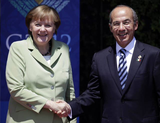 German Chancellor Angela Merkel, left, greets Mexico's President Felipe Calderon as they pose for pictures during the opening ceremony of the G20 Summit in Los Cabos, Mexico, Monday, June 18, 2012. (AP Photo/Eduardo Verdugo)