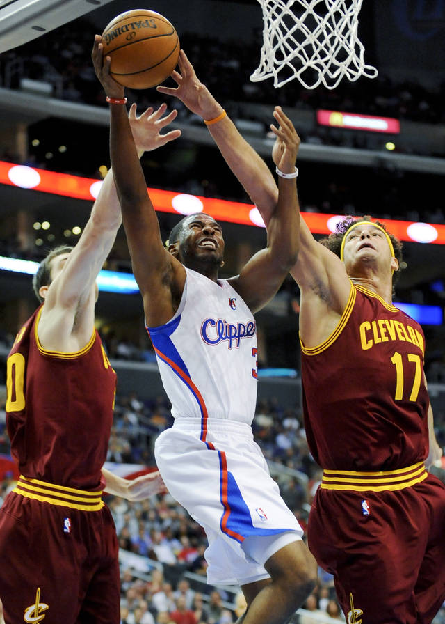 Los Angeles Clippers guard Chris Paul, center, drives between Cleveland Cavaliers forward Tyler Zeller, left, and center Anderson Varejao (17) in the first half of an NBA basketball game, Monday, Nov. 5, 2012, in Los Angeles. (AP Photo/Gus Ruelas)