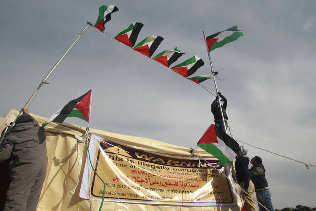 Palestinian activists place Palestinian flags in the new 'outpost ' of Bab al-Shams (Gate of the Sun) in an area known as E1, near Jerusalem, Saturday, Jan 12, 2013. Palestinian activists pitched tents in the West Bank on Friday to protest Israeli plans to build a large Jewish settlement on a key route through the territory. The E-1 settlement would block east Jerusalem from its West Bank hinterland � both territories captured by Israel during the 1967 Mideast war. (AP Photo/Nasser Shiyoukhi)