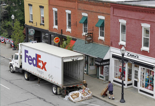 FILE - In this Wednesday, May 23, 2012, file photo, A Federal Express truck makes a delivery in downtown Chagrin Falls, Ohio.  FedEx said Tuesday, Dec. 4, 2012, that it will be offering some employees up to two years' pay to leave the company starting next year. The voluntary program is part of an effort by the world's second-biggest package delivery company to cut annual costs by $1.7 billion within three years. (AP Photo/Amy Sancetta, File)