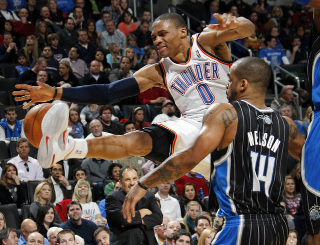 Oklahoma City's Russell Westbrook (0) has the ball knocked away as he is fouled by Orlando's Jameer Nelson (14) during the NBA basketball game between the Orlando Magic and Oklahoma City Thunder in Oklahoma City, Thursday, January 13, 2011. Oklahoma City won, 125-124. Photo by Nate Billings, The Oklahoman
