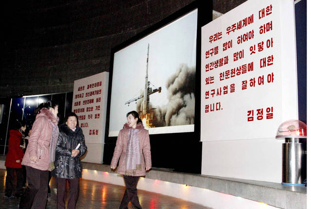FILE - In this Dec. 12, 2012 file photo, North Korean staff at the Three Revolution Exhibition Hall chat with one another inside the Satellite Hall after hearing the news of a rocket launch earlier on the day in Pyongyang, North Korea. North Korea's missile program is a point of national pride, with state TV regularly broadcasting past liftoffs set to rousing military anthems. But Pyongyang provides precious few details about its program's inner workings, leaving outside analysts to squeeze details from satellite photos and comparisons with other countries' missiles. (AP Photo/Kim Kwang Hyon, File) ORG XMIT: TOK117