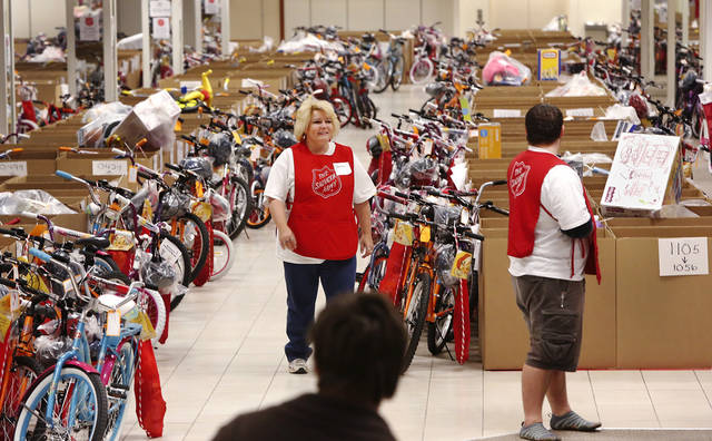 Volunteers walk among the boxes of gifts and the bicycles lined up for distribution inside the former Penney's store in Crossroads Mall. The Salvation Army and Feed the Children teamed to distribute bicycles and toys for children,  and handed out boxes of food for families at their annual distribution event Wednesday, Dec. 19, 2012. Salvation Army officials said 100 volunteers helped make the event go smoothly. The volunteers loaded bags of toys and bikes into vehicles of clients who had been pre-approved for assistance.  Many of the gifts were provided through the Salvation Army's Angel Tree program   Photo by Jim Beckel, The Oklahoman