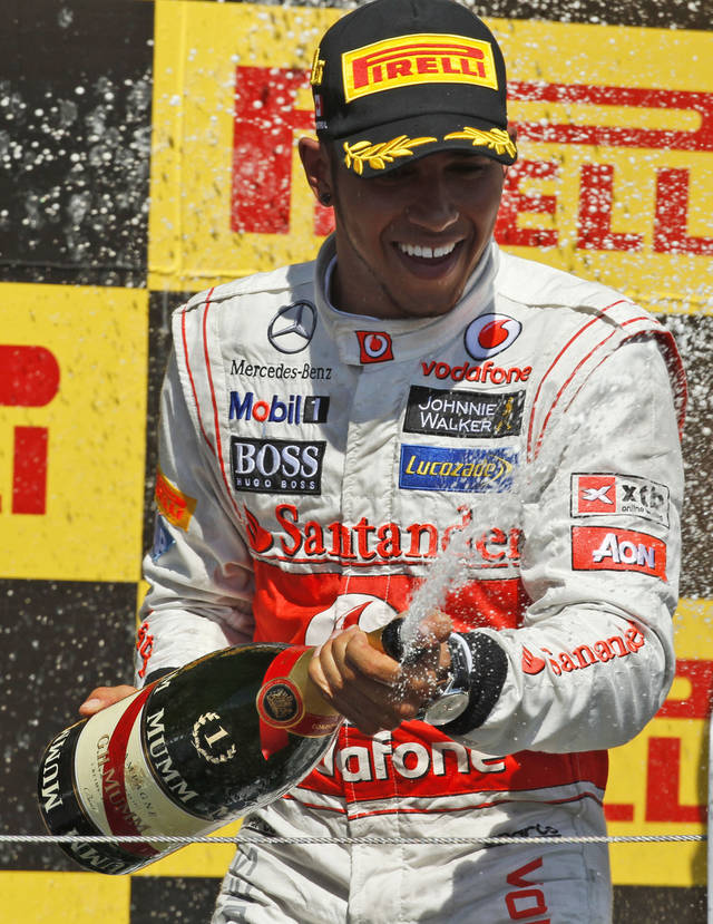 McLaren Mercedes driver Lewis Hamilton of Britain celebrates on the podium after winning the Canada Formula One Grand Prix, at the Gilles Villeneuve racetrack, in Montreal, Canada, Sunday, June 10, 2012. (AP Photo/Luca Bruno)