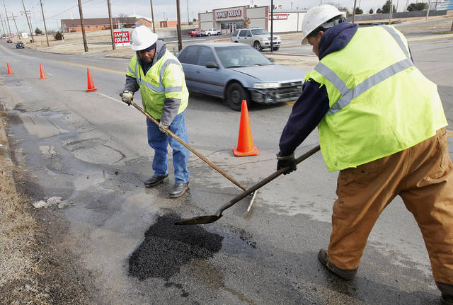 Ali Khalid, left, and Dwayne Gouge, pothole patchers with the Oklahoma City Street Maintenance Department, filling in a pothole in the 3300 block of N Kelley Avenue in Oklahoma City Friday, Jan. 13, 2012. Photo by Paul B. Southerland, The Oklahoman