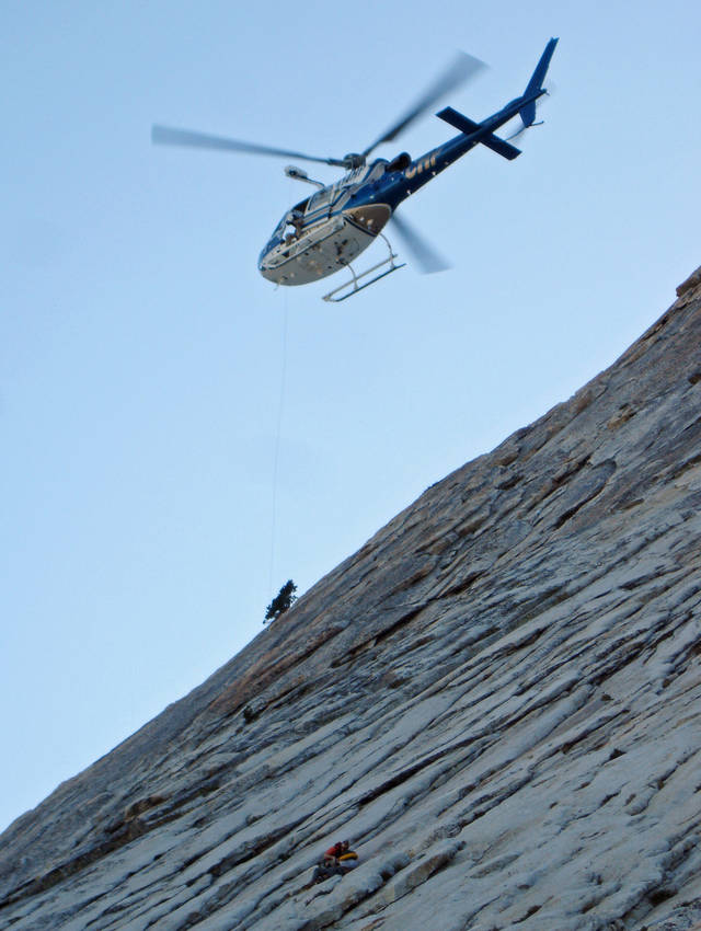 In this Saturday July 28, 2012 photo released by the Fresno County Sheriff's Department, a helicopter and Fresno County Sheriff's search and rescue team member rescue a Santa Barbara, Calif. man from a rocky ledge on Dog Tooth Peak in the Sierra Nevada, 45 miles northeast of Fresno, Calif. A hiker weary from clinging to the side of a Sierra peak for days was rescued by a sheriff's deputy who sprinted 300 feet up the 45-degree slope just as the hiker was losing his grip. (AP Photo/Fresno County Sheriff's Department)