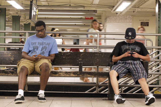 A couple of men use their smartphones at the Union Square subway station in New York. T-Mobile USA said Wednesday that it will start selling an unlimited-data plan again on Sept. 5. AP Photo