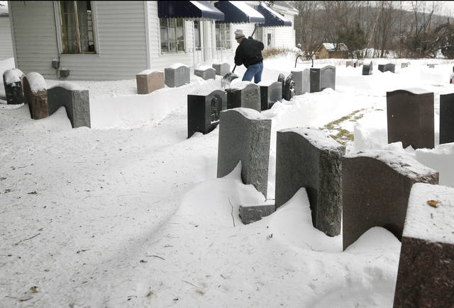 Rick Atwood clears memorial stones at Atwood Memorial Company in Haverhill, Mass. Monday, Feb. 11, 2013. Beleaguered Massachusetts residents returned to work on Monday for the first time since the weekend blizzard, crawling along narrow snow-covered secondary roads and being greeted by a new wintry mix of sleet and freezing rain. (AP Photo/Elise Amendola)