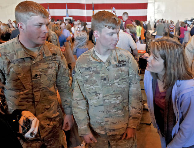 Kristy Brock talks to her two sons, Jake and Justin Farrow, from left, during the return ceremony for more than 200 National Guard 45th Infantry Brigade Combat Team troops at the National Guard Base on Monday, March 12, 2012, in Oklahoma City, Oklahoma.  Photo by Chris Landsberger, The Oklahoman