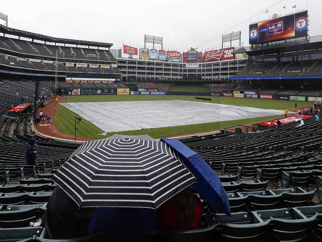 Fans wait in a light rain for the start of a baseball game between the Texas Rangers and the Seattle Mariners, Sunday, Sept. 16, 2012, in Arlington, Texas. (AP Photo/Jim Cowsert)