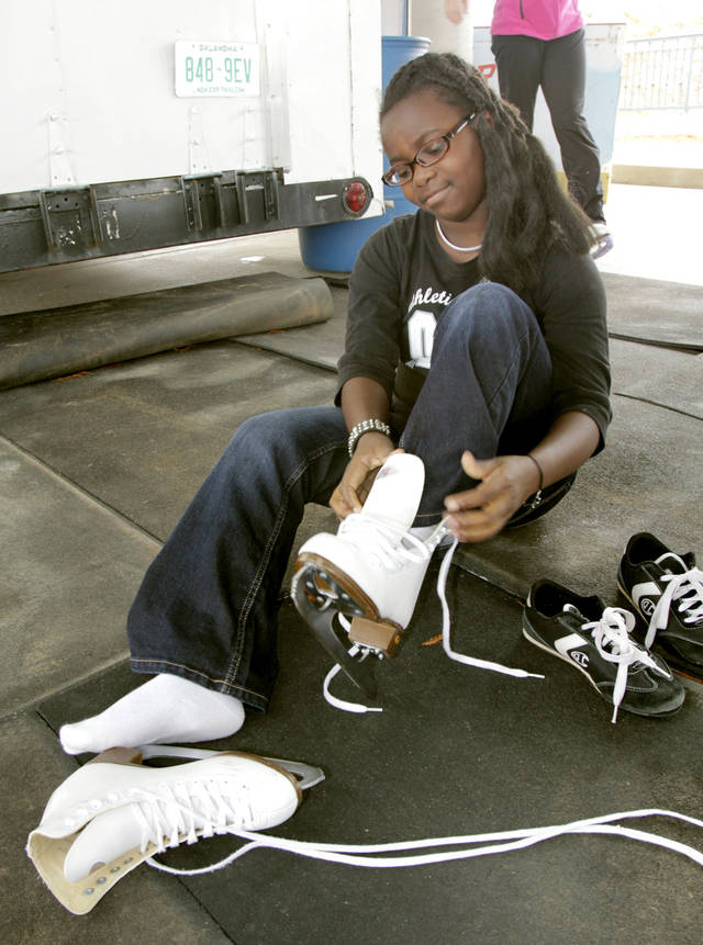 Eleven-year-old Uzima Mangrum gets her new skates on as an outdoor skating rink opens at Edmond's Festival Market Place in Edmond, OK, Friday, Nov. 25, 2011. By Paul Hellstern, The Oklahoman