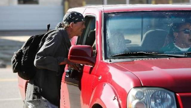 A homeless man leans into a truck window to hear about work possibilities. Men congregate in a parking lot to wait for people driving through looking to hire day laborers. Many downtown homeless stay in the area along Sheridan, California and Reno between Walker and Western. Photo taken Wednesday, Oct. 21, 2010. Photo by Jim Beckel, The Oklahoman